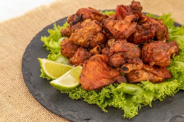 Porción de pollo frito en placa de piedra negra.