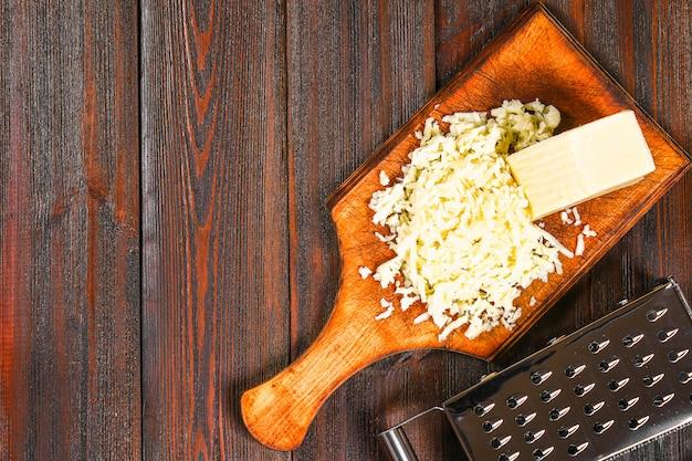 Porción de queso cheddar rallado en la tabla de madera rústica.