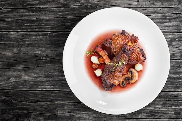Porción de sabroso estofado de pollo de muslo y muslo al vino y verduras