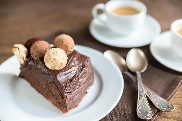 Porción de torta sacher con dos tazas de café.