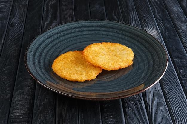 Porción de tortitas de patata fritas en mesa de madera oscura