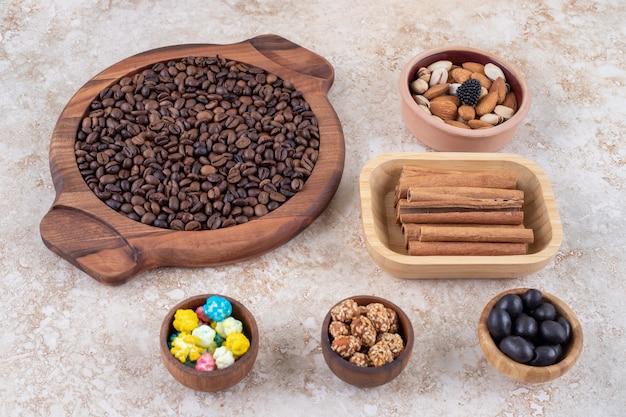 Porciones de caramelos, frutos secos variados, cacahuetes glaseados, palitos de canela y granos de café.