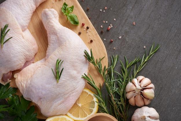 Porciones de carne de pollo fresca para cocinar y asar a la parrilla con condimentos frescos. muslo de pollo crudo crudo sobre tabla de cortar.