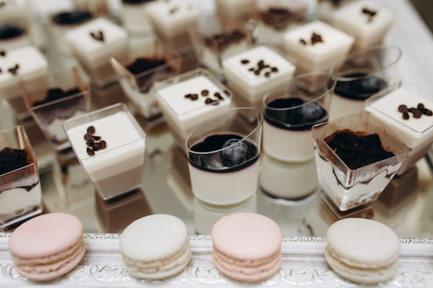 Porciones de tiramisú, postres de mousse y macarons