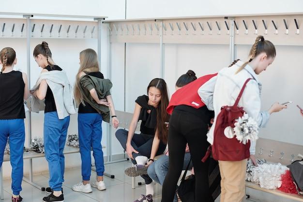 Porristas adolescentes en ropa casual, cambio de vestido y zapatos mientras se preparan para el entrenamiento en vestuario