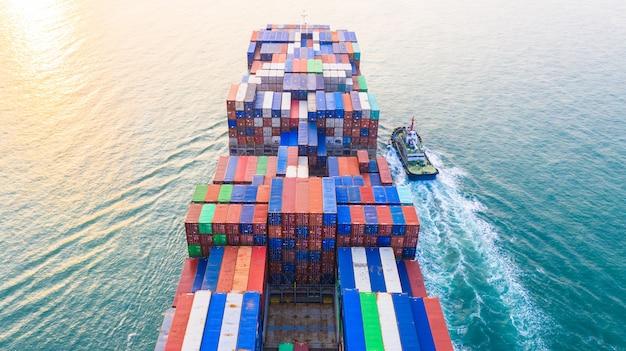 Portacontenedores que llegan al puerto, portacontenedores y remolcadores que van al puerto marítimo, negocios logísticos, importación, envío y transporte, vista aérea.