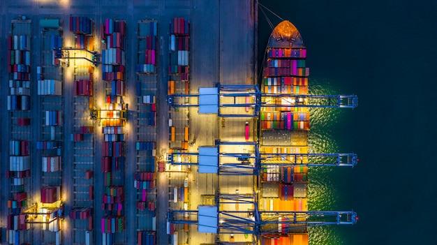Portacontenedores trabajando de noche, logística de importación y exportación de negocios y transporte.