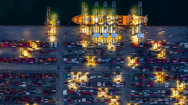 Portacontenedores trabajando por la noche, logística de importación y exportación de negocios.