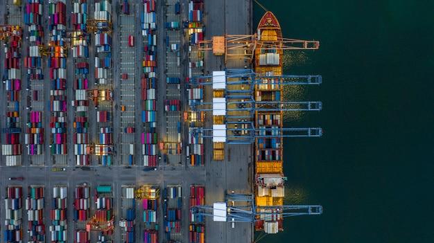 Portacontenedores de la vista aérea que carga en la noche en puerto industrial.
