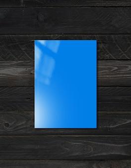 Portada del folleto azul aislado sobre fondo de madera negra