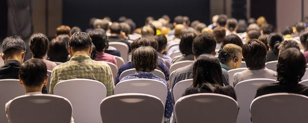Portada de la portada de la vista posterior de la audiencia escuchando oradores en el escenario