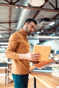 Portadas de libros. escritor barbudo mirando las muestras de portadas de libros que trabajan en la oficina de impresión