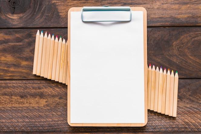 Portapapeles acostado en el conjunto de lápices