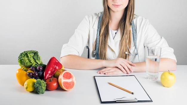 Portapapeles en blanco; comida saludable y vaso de agua en el escritorio