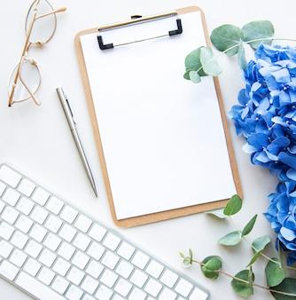 Portapapeles blanco con flores azules y teclado