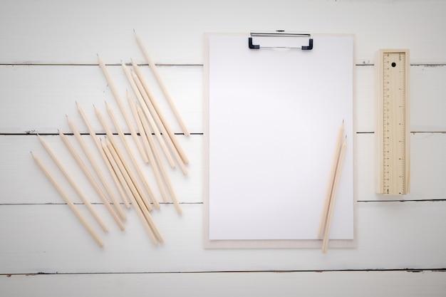Portapapeles blanco con papel en blanco, lápices, regla y caja de madera en
