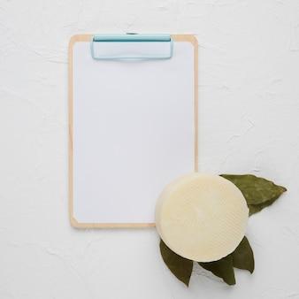 Portapapeles en blanco con queso manchego español y hojas secas de laurel sobre fondo blanco de concreto