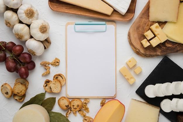 Portapapeles en blanco rodeado de delicioso ingrediente sobre fondo liso