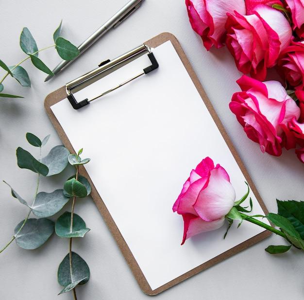 Portapapeles en blanco con rosas rosadas, sorpresa en el trabajo para san valentín