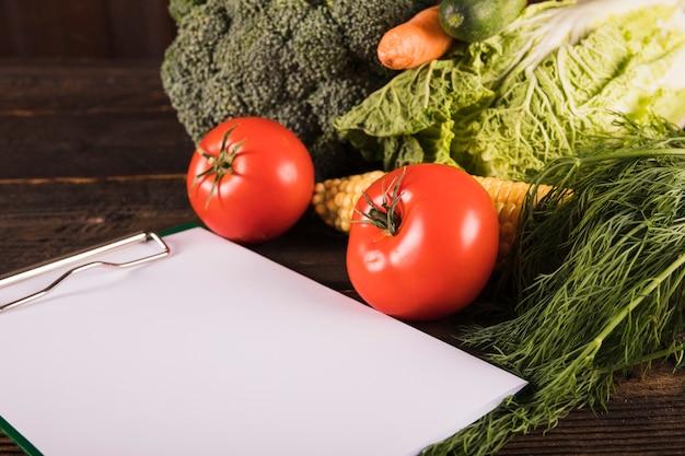 Portapapeles en blanco y verduras crudas frescas en el escritorio