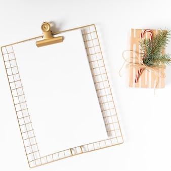 Portapapeles con caja de regalo en mesa blanca