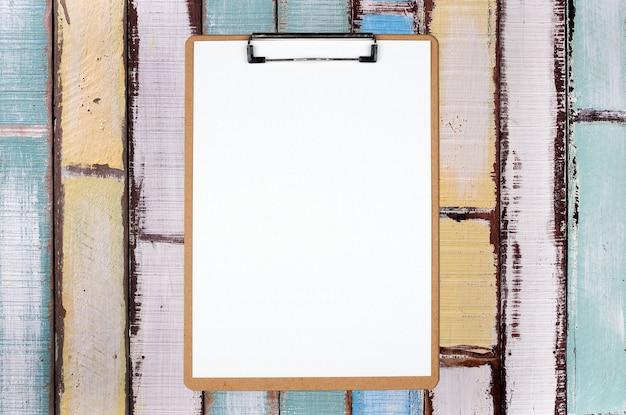 Portapapeles con hoja en blanco sobre fondo de madera de colores