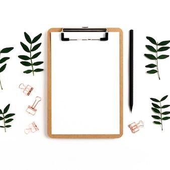 Portapapeles imitan para arriba. clips de papel, lápiz, ramas de pistacho sobre un fondo blanco
