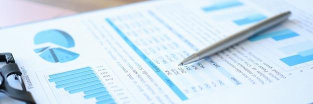 Portapapeles con informe financiero y bolígrafo se encuentran en la mesa de desarrollo de pequeñas y medianas empresas