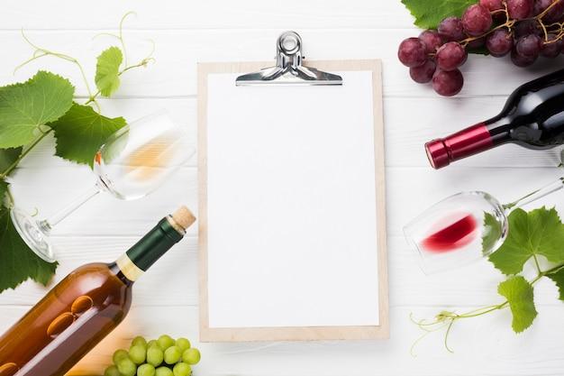 Portapapeles maqueta rodeada de botellas de vino.