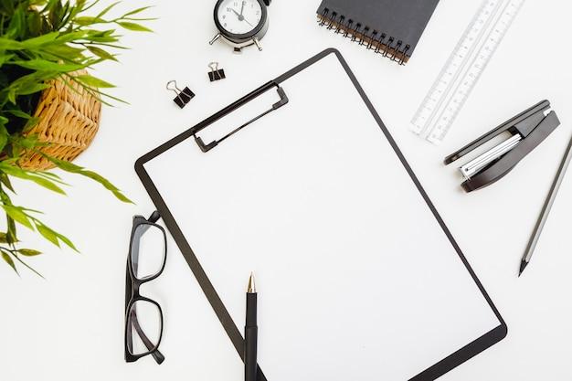Portapapeles con material de oficina en mesa blanca, vista superior