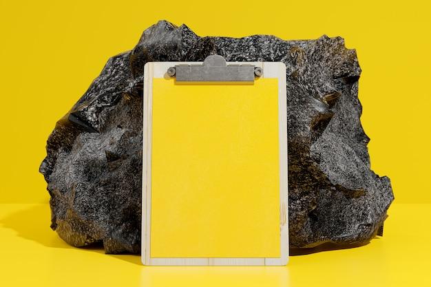 Portapapeles mock-up de color amarillo frente a la piedra negra. render 3d.