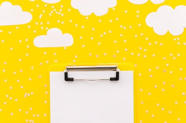 Portapapeles con nubes de papel en la mesa