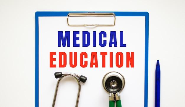 Portapapeles con página y texto educación médica, sobre una mesa con un estetoscopio y bolígrafo