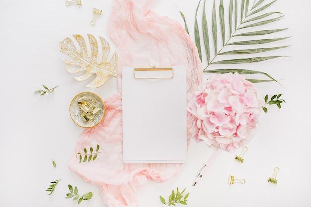 Portapapeles de papel en blanco, flores de hortensia rosa y accesorios en superficie blanca