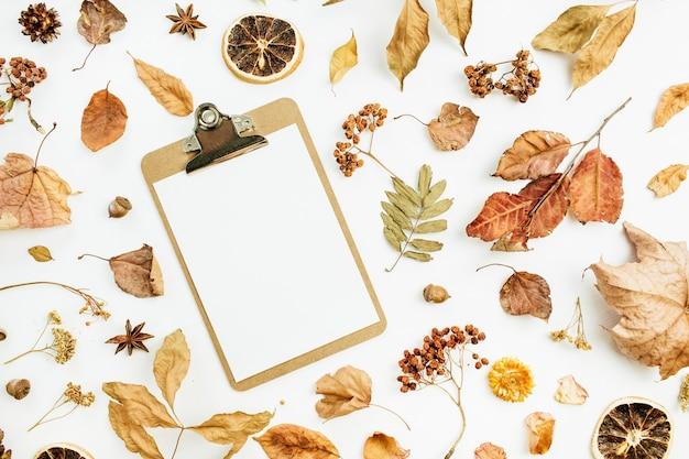 Portapapeles con papel en blanco con hojas de otoño secas, pétalos y naranjas sobre superficie blanca