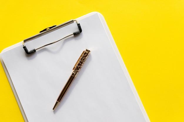 Portapapeles con papel en blanco. portapapeles negro con papel blanco en blanco vacío con bolígrafo, en la pared amarilla espacio de copia de texto. diseño minimalista, concepto de espacio de trabajo.