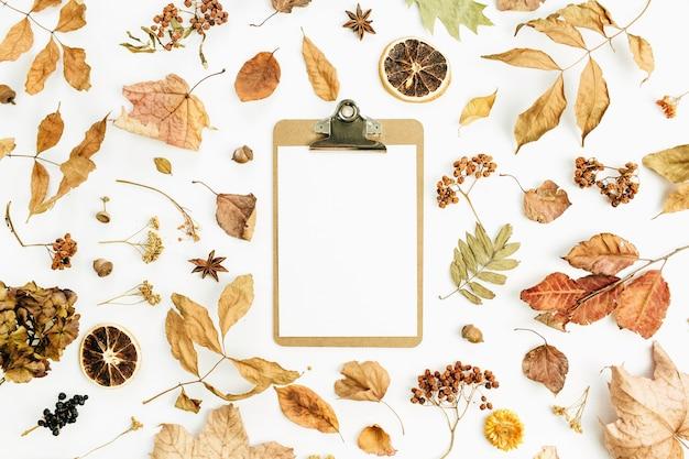 Portapapeles con papel en blanco sobre la superficie seca de las hojas de otoño de otoño