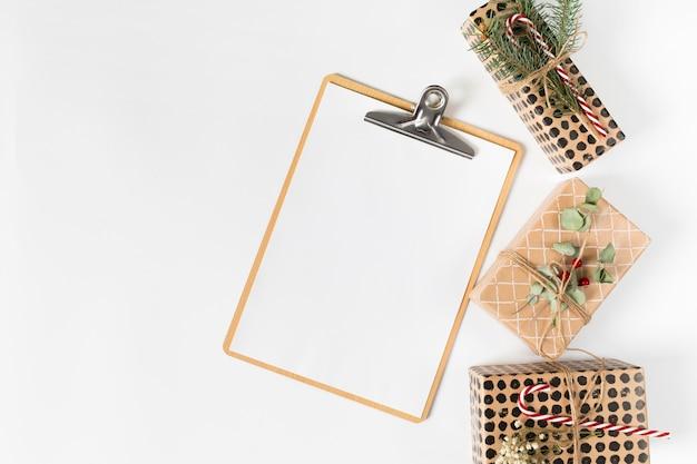 Portapapeles con pequeñas cajas de regalo en mesa de luz