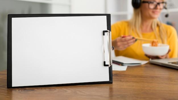 Portapapeles de primer plano en el escritorio con mujer detrás