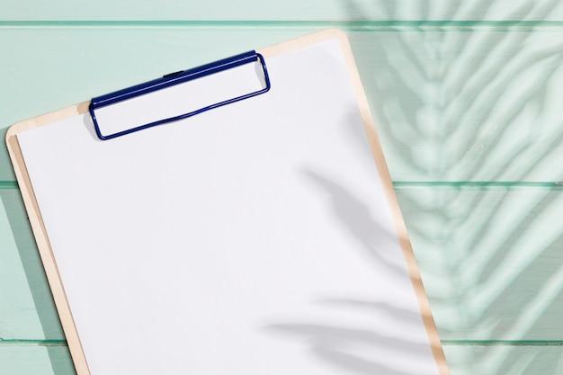 Portapapeles de primer plano con espacio de copia y hojas de sombra