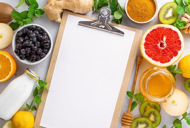 Portapapeles con productos saludables para mejorar la inmunidad vista desde arriba. verduras y frutas para estimular el sistema inmunológico.