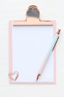 Portapapeles rosa y dorado con hoja de papel blanco, corazón de clip, bolígrafo rosa-azul sobre una mesa blanca. diseño plano, vista superior.