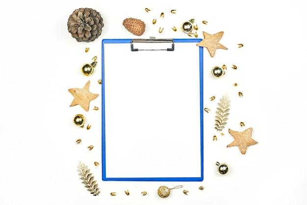 Portapapeles vacío decorado con adornos navideños, galletas en forma de estrella y piñas. decoraciones navideñas con papel en blanco