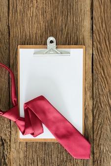 Portapapeles viejo, corbata roja en superficie de madera sucia