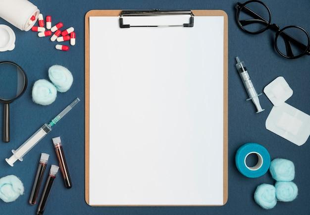Portapapeles de vista superior rodeado de herramientas médicas