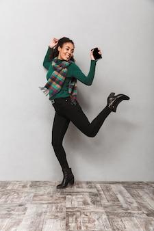 Portarit de longitud completa de una bonita mujer africana con bufanda saltando, sosteniendo el teléfono móvil
