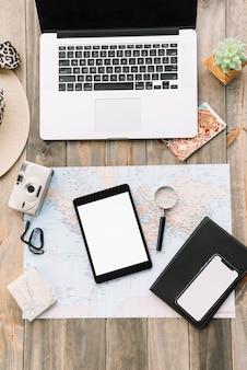 Un portátil abierto con cámara; tableta digital; lupa; diario y celular en el mapa