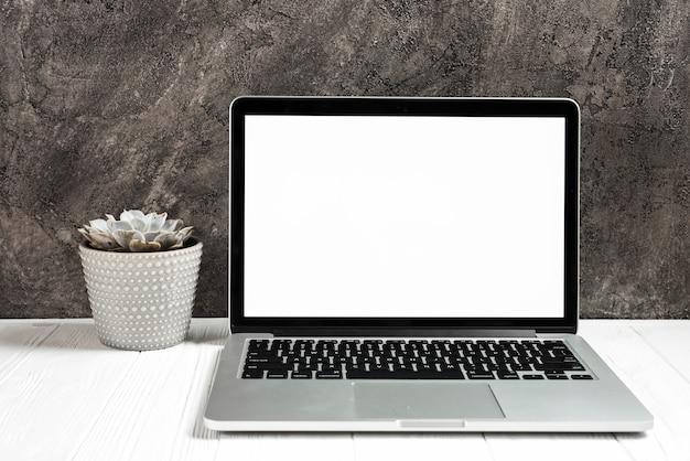 Un portátil abierto con pantalla blanca en blanco en el escritorio de madera contra una pared negra