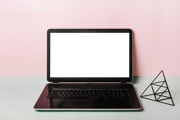 Un portátil abierto con pantalla blanca en blanco sobre fondo rosa