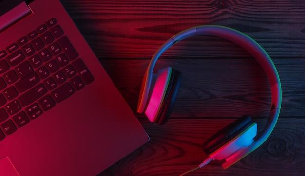 Portátil y auriculares con luz neón azul-roja